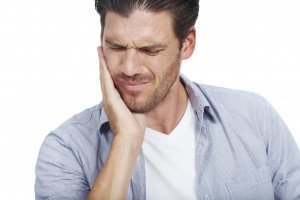 Man rubbing cheek from annoying tooth pain
