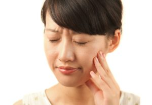 Woman closes eyes as she suffers form toothache