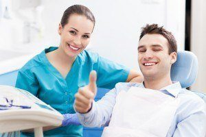 New patient finishes his first dental appointment, gives thumb up with dentist