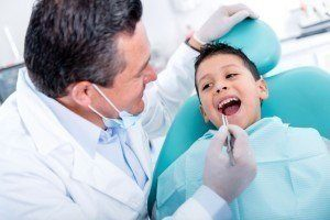 Boy patient having his mouth examined at Advanced Dental Group where he gets his pediatric dentistry services.